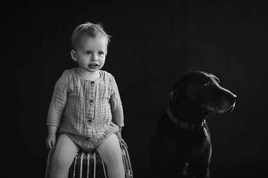 A black and white photograph of child and dog in a studio. Photographed by Shan Radford