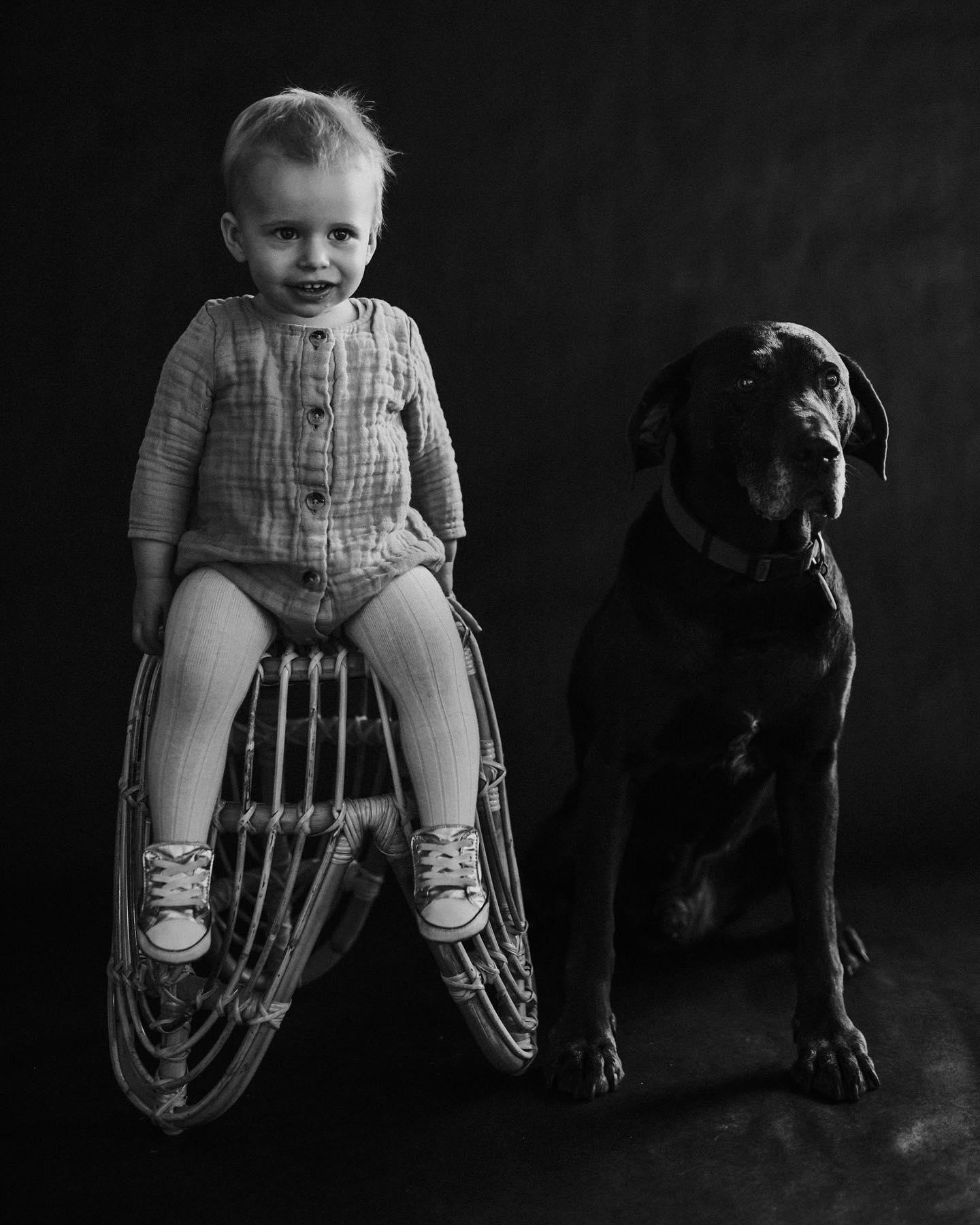 black and white studio portrait of Child and pet dog
