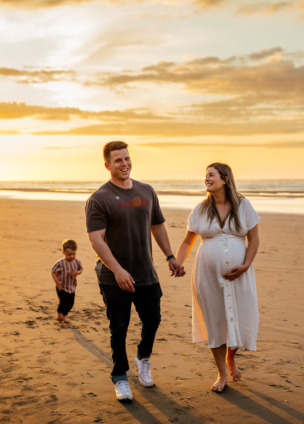 Family at the beach during sunset having maternity photos taken by Shan Radford
